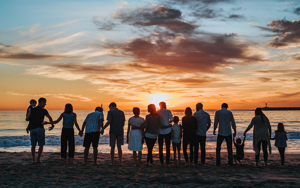 Large family watches sunset on the beach