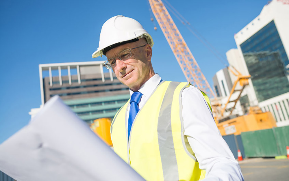 Man looks at blueprints on a construction site