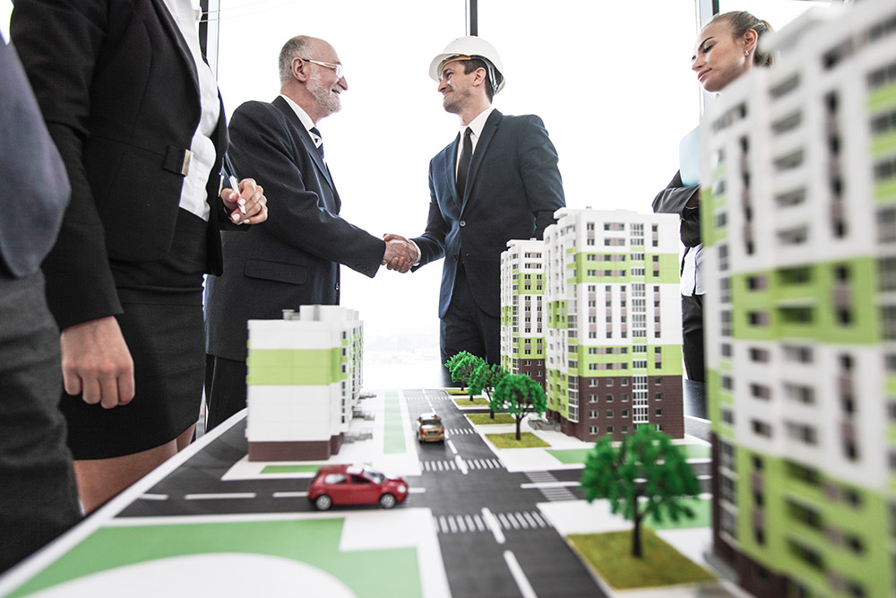 People shake hands over models of new developments