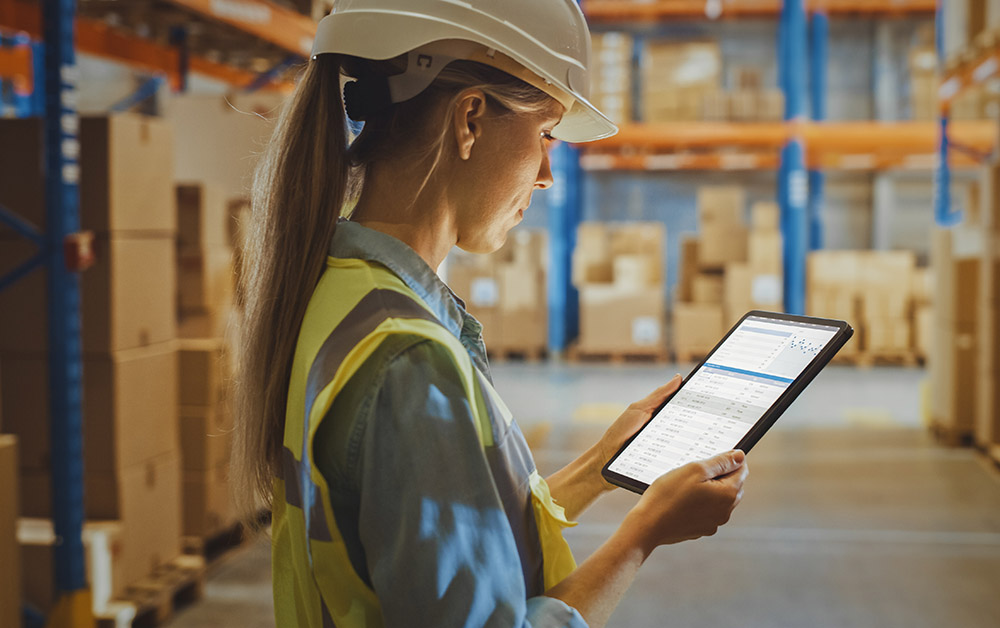 A woman views her tablet in a warehouse